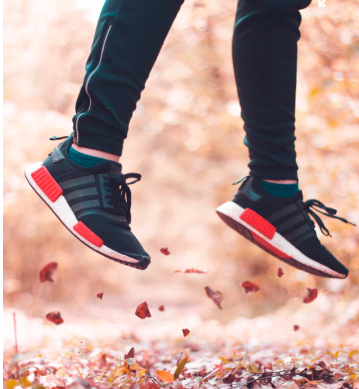 person jumping in autumn leaves